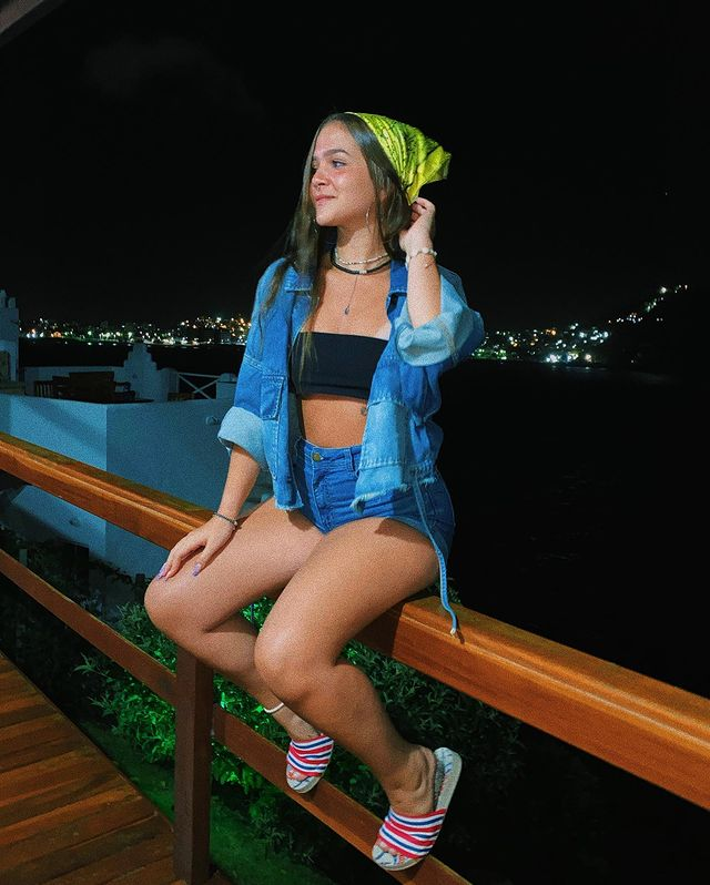 A atriz Mel Maia usando jaqueta jeans com top faixa preto e short jeans de lavagem azul. Ela está sentada em cima de um corrimão de madeira, com uma das mãos no cabelo, que tem uma bandana verde neon, e, nós pés, um chinelo slide branco de listras vermelhas, brancas e azuis.