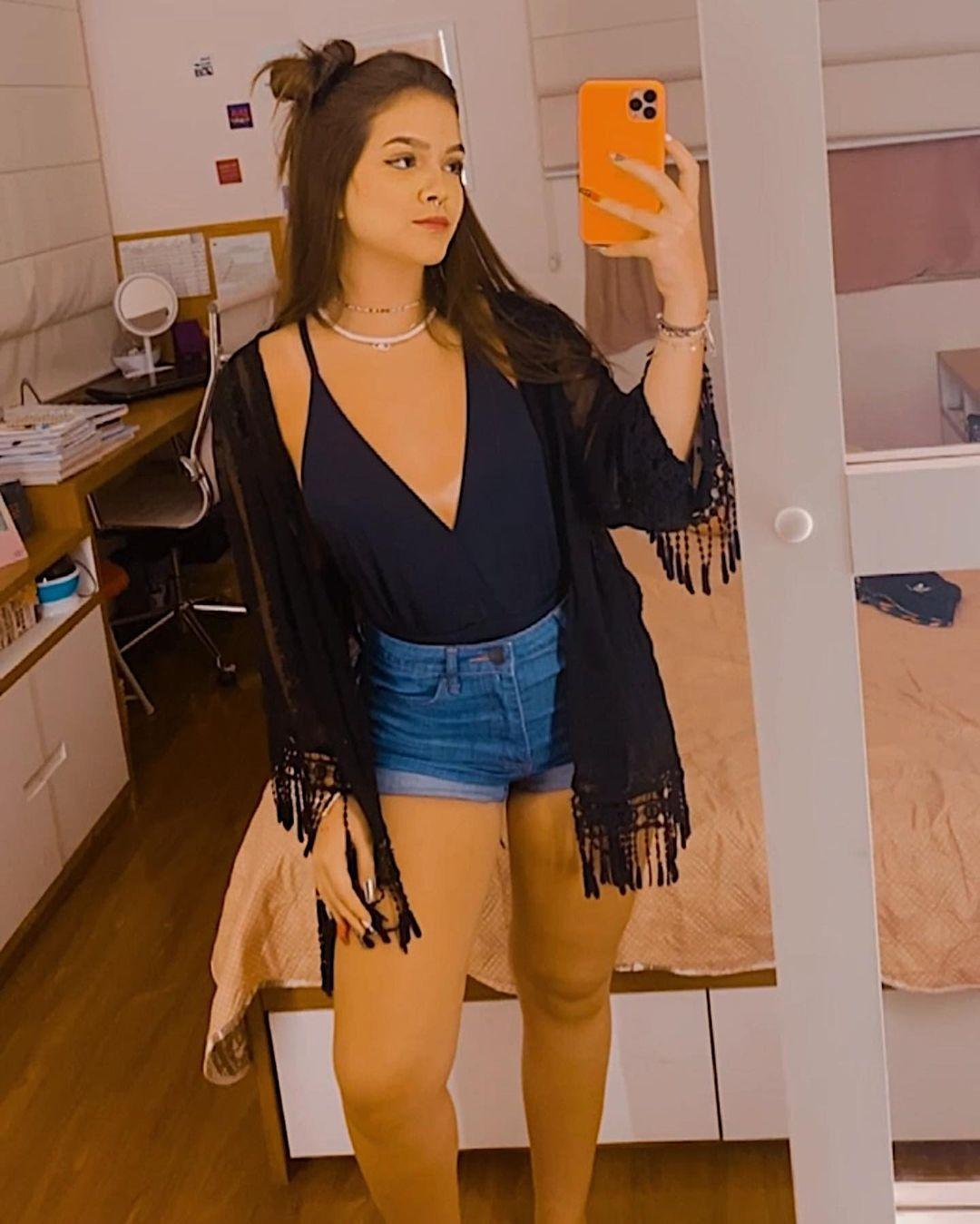 A atriz Mel Maia usando look com body preto com decote V, short jeans e kimono preto com franjas por cima. Ela está em pé, em frente a um espelho, com expressão facial séria, olhando para o celular que ela segura com uma das mãos.