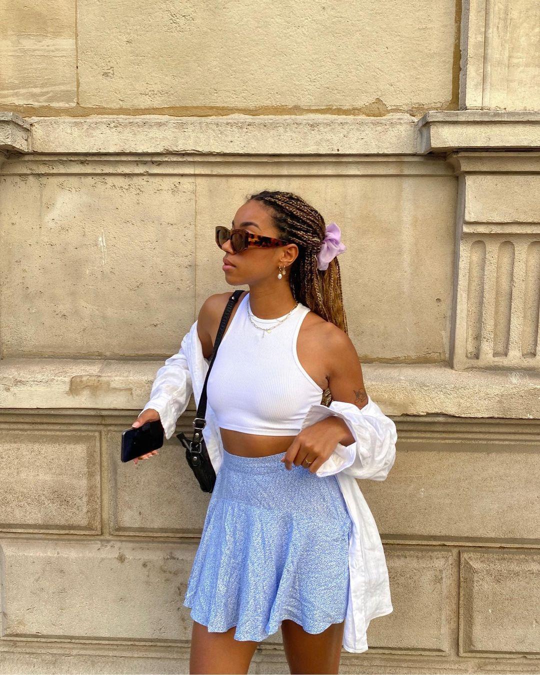 Garota usando top cropped branco com saia rodada azul e camisa branca por cima. Ela está com uma bolsa preta pendurada em um dos ombros, segurando o celular em uma das mãos, cabelo preso em um rabo com scrunchie lilás e óculos de sol. Ela está olhando para o lado.