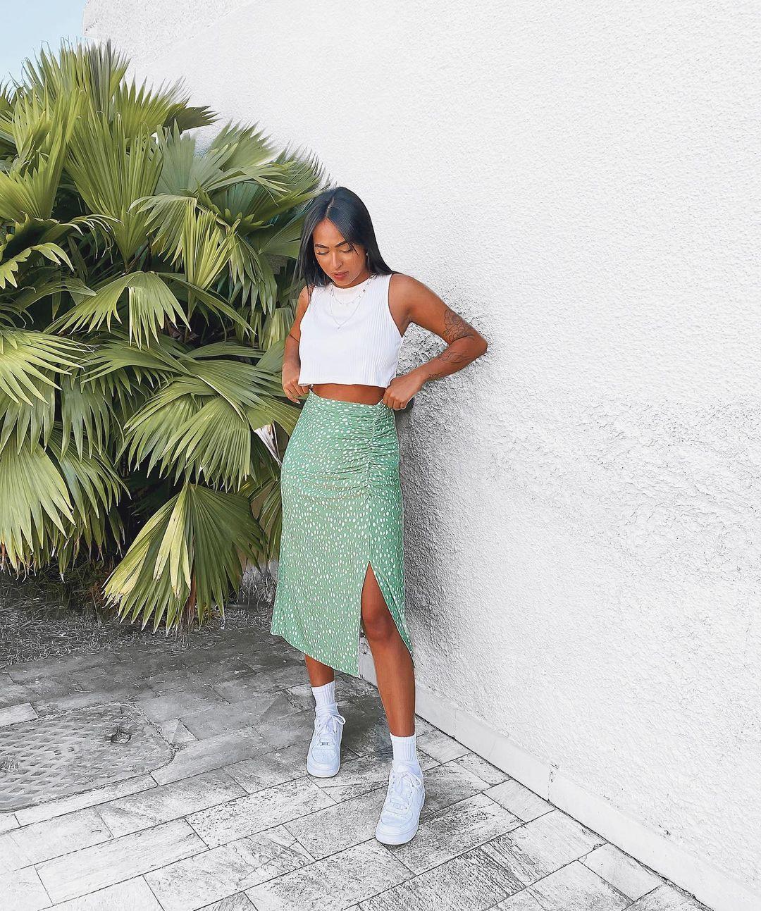 Garota usando top cropped branco com saia midi verde com bolinhas brancas e tênis e meia brancos. Ela está olhando para baixo com as duas mãos arrumando a blusa.