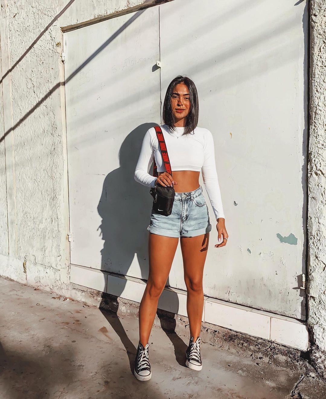 Garota usando top cropped branco de manga longa com short jeans e tênis All Star preto e branco de cano alto. Em pé, ela está segurando uma minibolsa de alça longa em um dos ombros.