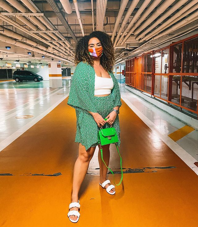 Garota usando top cropped branco com kimono e bermuda estampados em verde com bolinhas brancas. Ela está em pé, usa uma rasteirinha branca de duas tiras, segura uma bolsa verde neon na frente do corpo e está com uma máscara de proteção laranja e rosa.