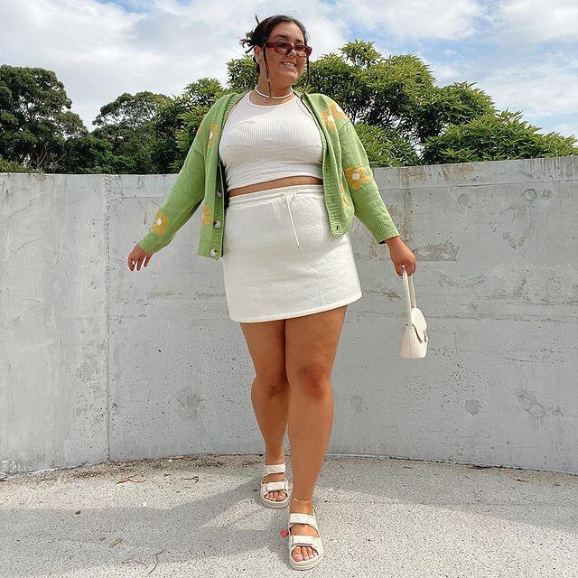 Garota usando top cropped branco, saia de tricô branca e papete branca. Ela está com um cardigan verde com flores amarelas. Ela está em pé, uma das mãos segura uma minibolsa branca e está com óculos de sol. Ela está sorrindo.