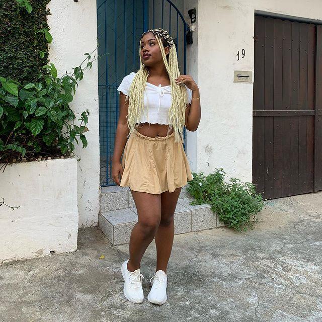 Garota usando top cropped branco com saia bege e tênis branco. Ela está olhando para os lados com uma das mãos no cabelo comprido.