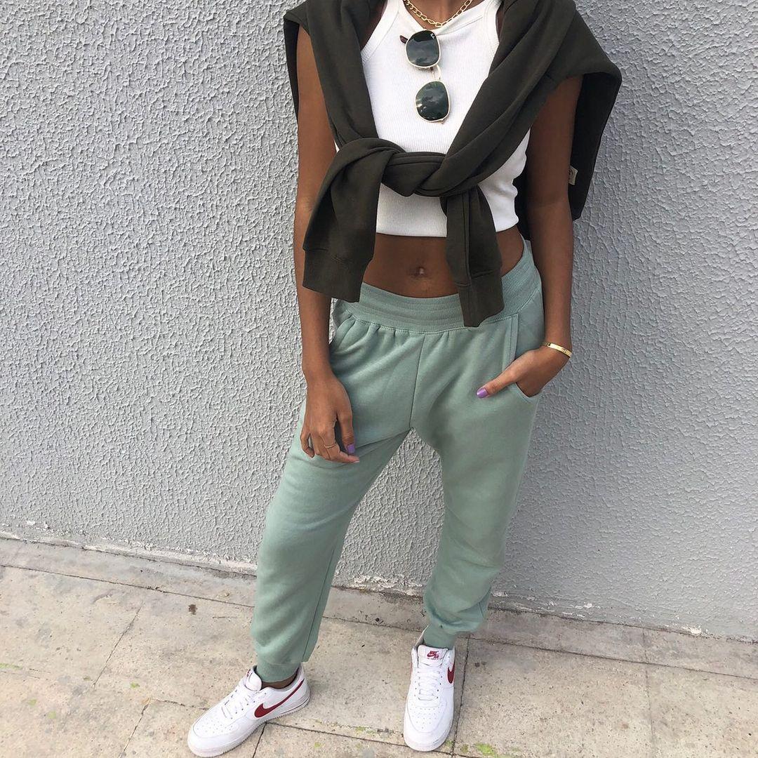 Garota usando top cropped branco com calça de moletom verde, tênis branco e suéter preto amarrado nos ombros. Tem um óculos de sol pendurado na gola da blusa, e a foto pega apenas do pescoço para baixo.