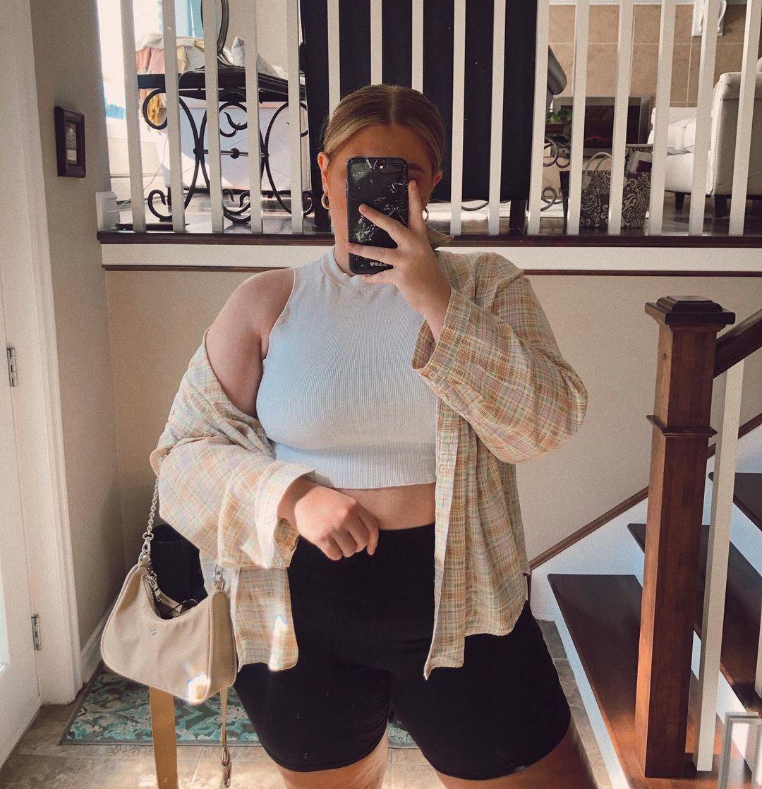 Garota usando top cropped branco com bermuda ciclista e camisa xadrez laranja e cinza por cima. Um dos braços segura uma bolsa bege com alça de corrente, e a outra mão segura o celular para tirar foto em frente ao espelho.
