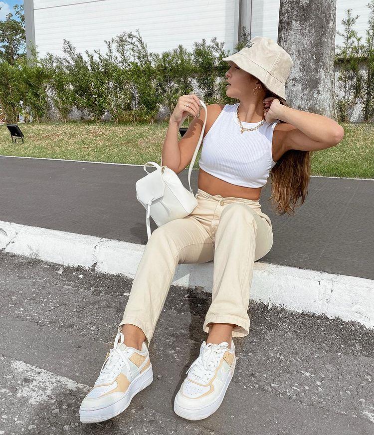 Garota está sentada na calçada usando top cropped branco, calça bege, tênis branco, bucket hat bege e minimochila. Ela está olhando para o lado, com uma das mãos atrás da nunca e a outra no ombro.