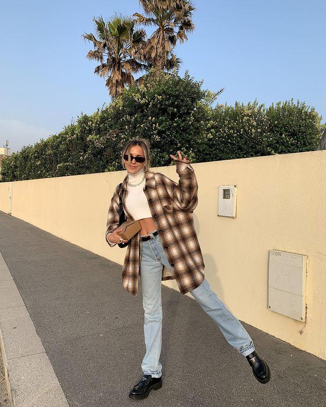 Garota usando top cropped branco com calça jeans, cinto preto, oxford preto e camisa xadrez marrom e branca por cima do look. Ela está com uma das pernas levantadas, uma mão segurando um pacote, a outra fazendo o símbolo de paz e amor com os dedos. Ela ainda usa um óculos de sol e sorri.