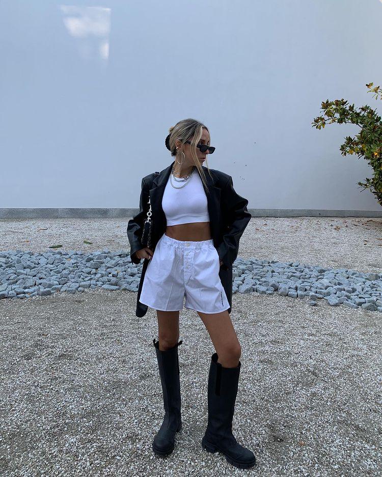 Garota usando top cropped branco com short branco de cintura alta, bota tratorada preta que vai até o joelho e um casaco de couro preto por cima. Ela está em pé, usando óculos de sol e uma bolsa preta em um dos ombros. Sua cabeça está inclinada para um dos lados, e um dos joelhos está dobrado.