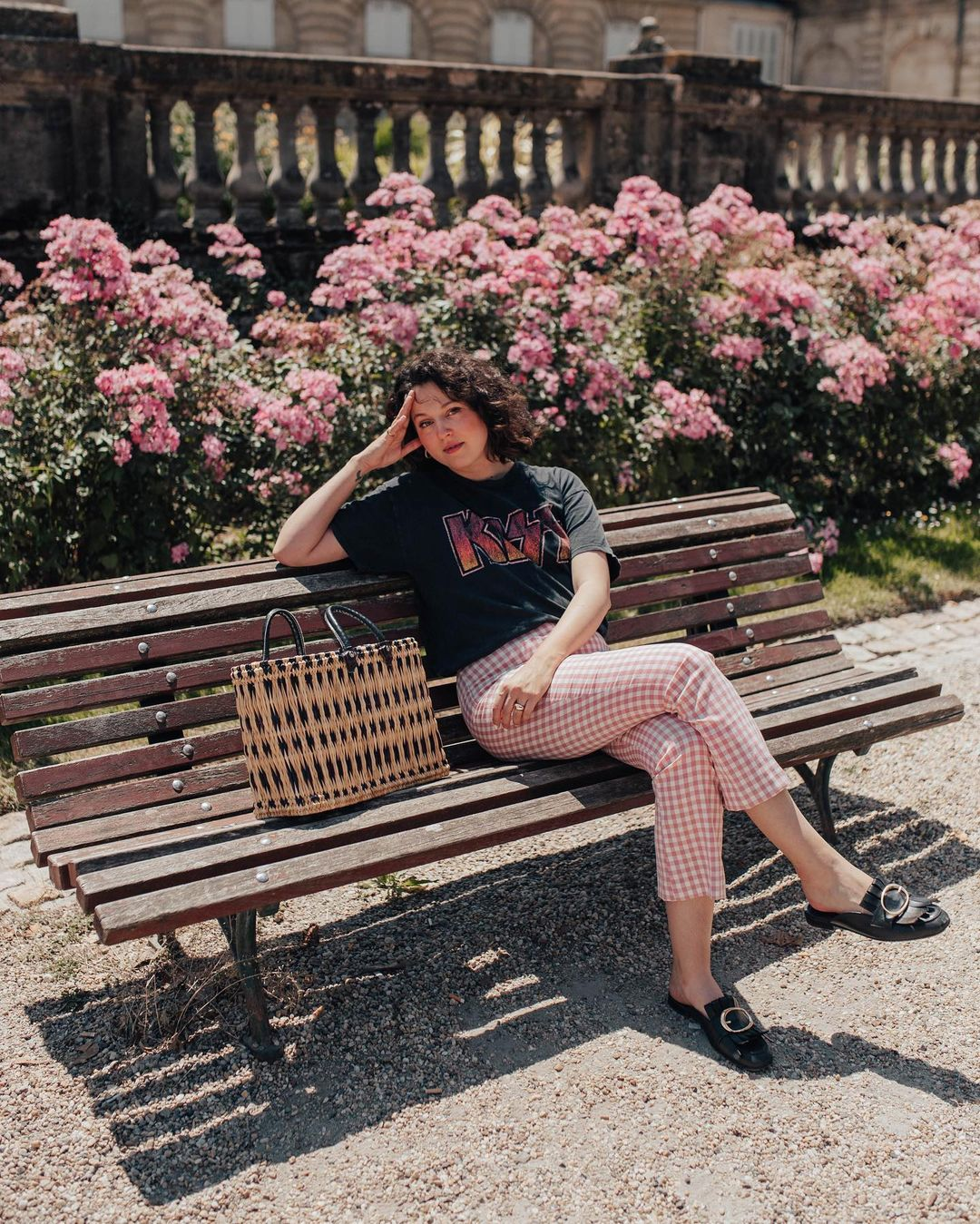 Garota usando look com calça xadrez vichy vermelha, camiseta preta da banda Kiss e oxford preto. Ela está sentada em um banco marrom, com uma das mãos apoiadas na coxa, e a outra na cabeça. Ao lado dela, tem uma maxibolsa de palha com detalhes em preto. Sua expressão facial é séria.