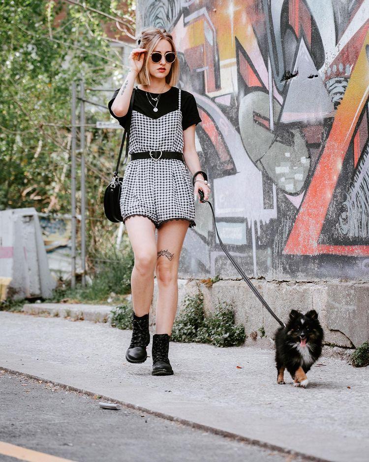 Garota usando look com macaquinho xadrez vichy preto e branco e camiseta preta de manga curta por baixo, além de um cinto preto. Nos pés, um coturno preto, uma bolsa preta pendurada em um dos ombros, e usando óculos de sol. Ela está em pé, com uma das mãos no cabelo, e a outra segura uma coleira de um cachorro pequeno de pelos em preto e branco.