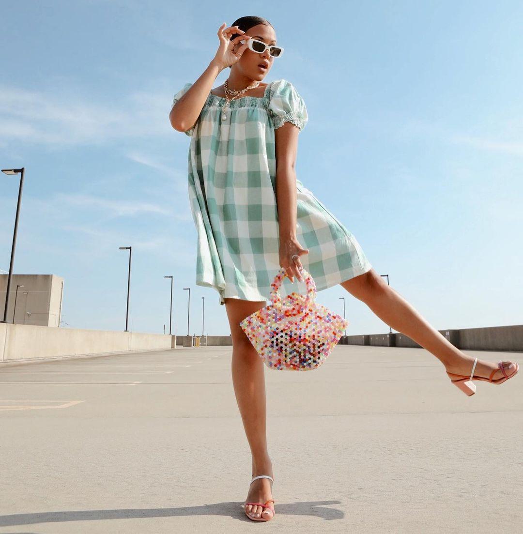 Garota usando look com vestido xadrez vichy verde e sandália branca e vermelha de tiras com saltinho. Com uma das mãos, ela segura os óculos de sol brancos, e com a outra uma bolsa de miçangas coloridas. Uma das pernas está levantada para o lado e sua expressão facial é de surpresa, com a boca aberta.