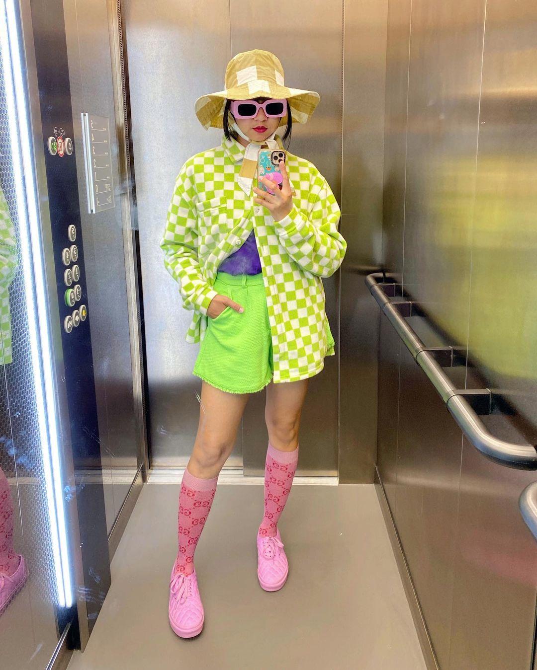 Garota usando casaco xadrez vichy verde com short verde neon, meia rosa até o joelho e tênis rosa, além de um chapéu xadrez vichy amarelo. Ela está em pé, em frente a um espelho, usando óculos de sol cor-de-rosa, com uma das mãos no bolso, e a outra segurando o celular para tirar a foto em frente ao espelho.