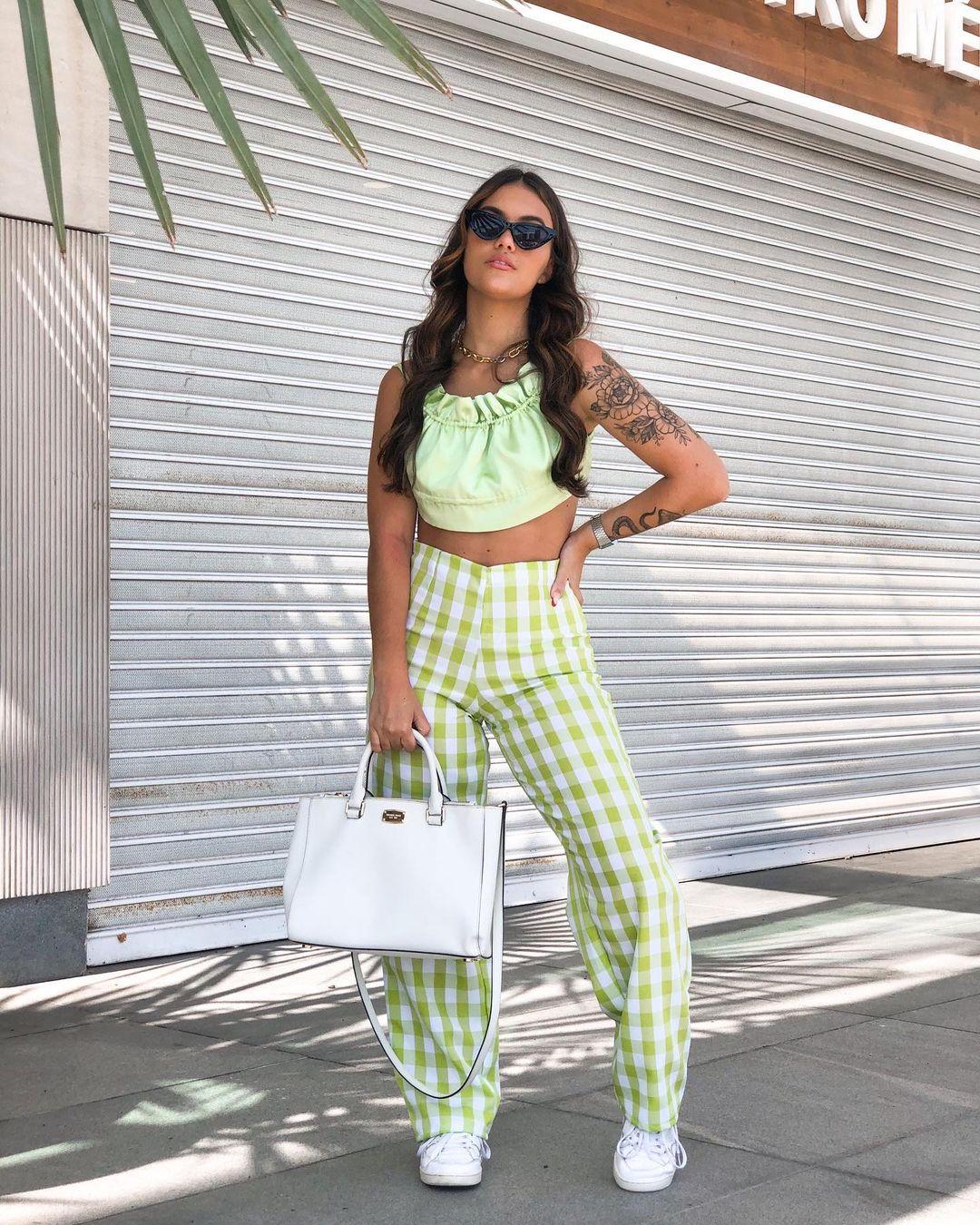 Garota usando top cropped verde com calça verde de xadrez vichy e tênis branco. Uma das mãos está segurando uma maxibolsa branca, e a outra está na cintura. Ela está com um óculos de sol no rosto, com a cabeça levemente levantada, olhando para baixo.