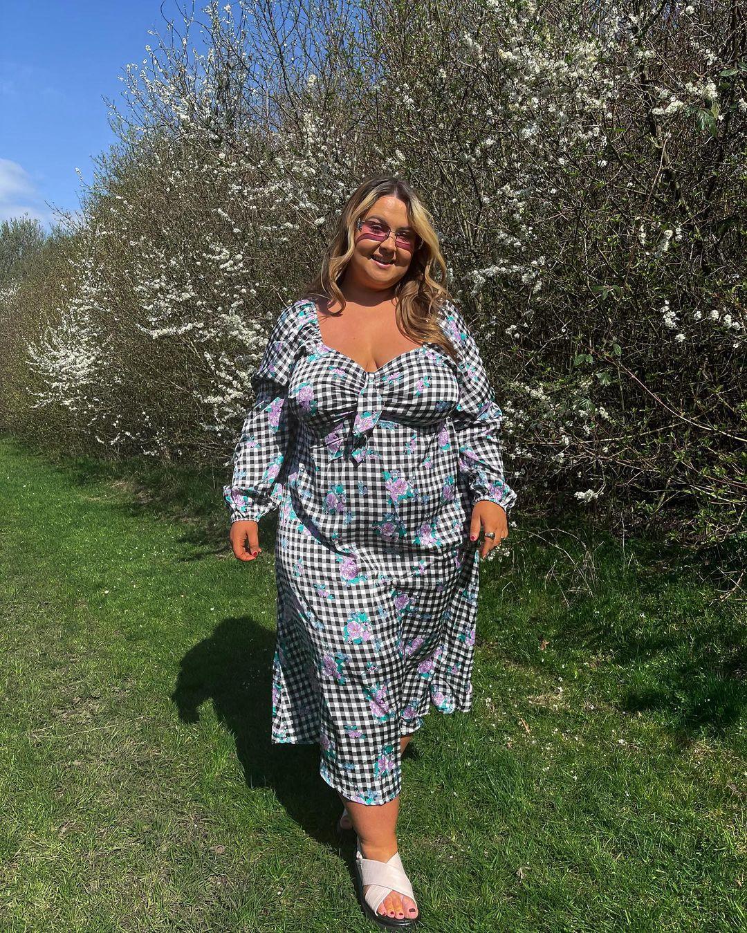 Garota usando look com vestido longo xadrez vichy preto e branco e algumas flores em rosa. Ela usa uma sandália branca, óculos de sol com lentes rosas, está em pé e sorrindo.