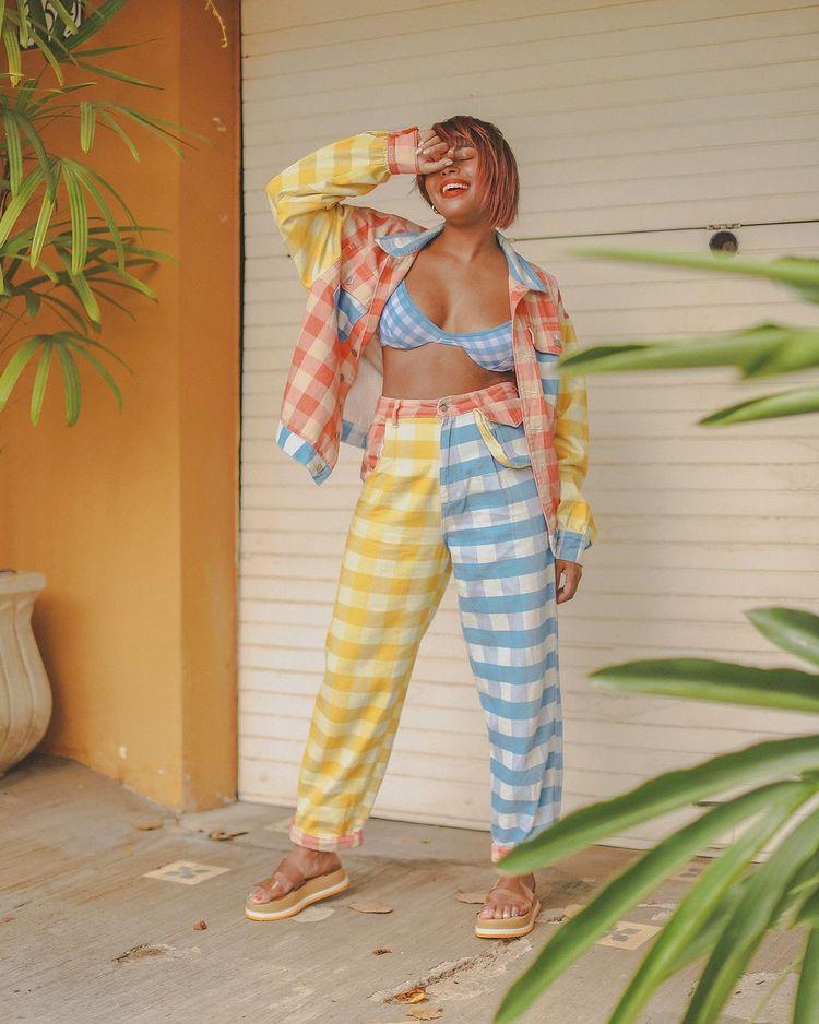 Garota usando conjuntinho xadrez vichy formado por top azul, calça amarela e azul e jaqueta amarela, vermelha e azul. Ela está em pé, com uma das mãos perto dos olhos, usando uma sandália papete e com sorriso no rosto.