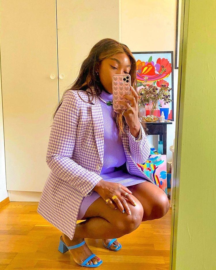 Garota usando blazer xadrez vichy lilás, vestido roxo e sandália de duas tiras azul. Ela está agachada em frente ao espelho, com uma das mãos em cima da coxa, e a outra segurando o celular para tirar a foto.