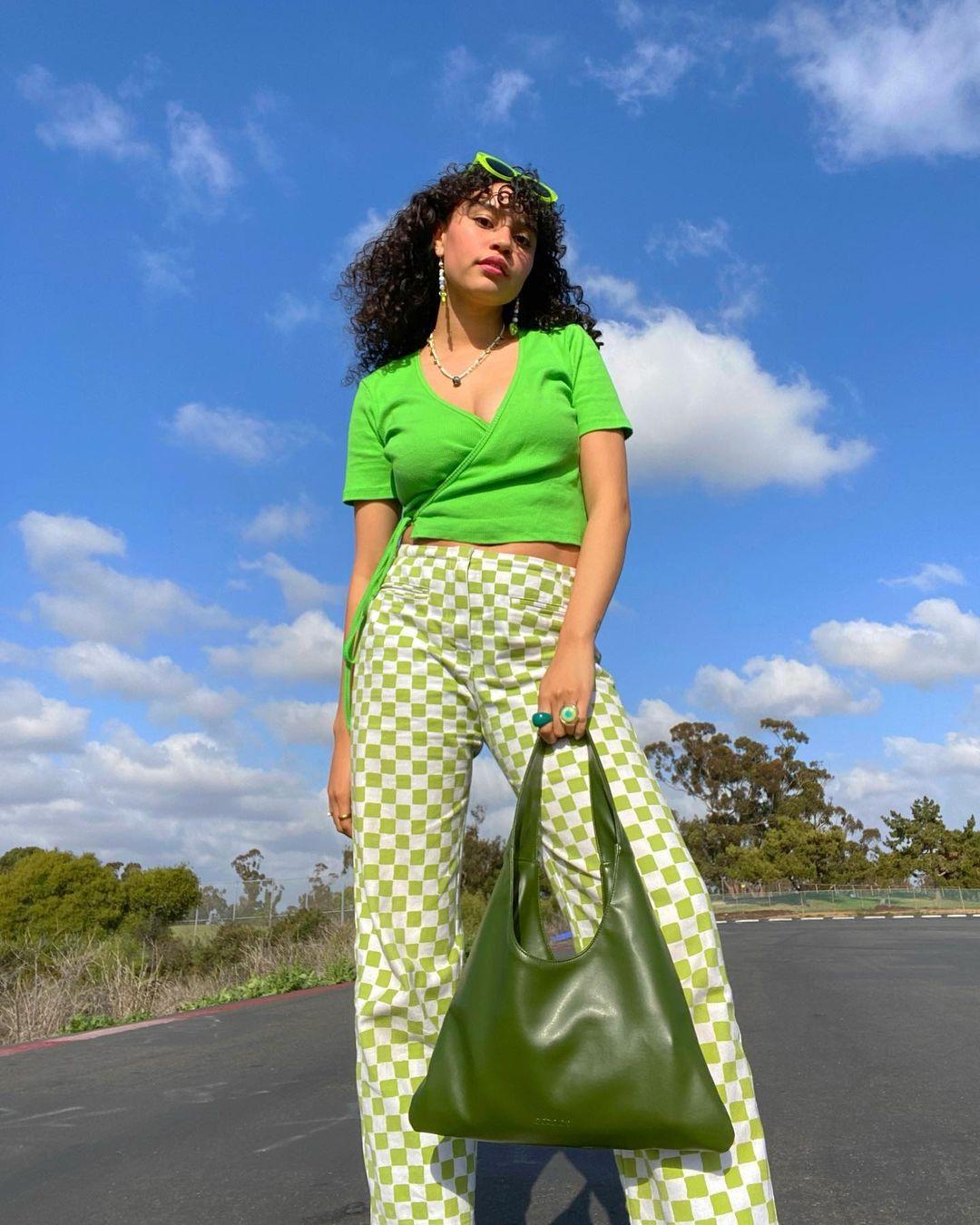 Garota usando blusa verde neon e calça xadrez vichy verde de cintura alta. Ela está em pé, com os óculos de sol verdes neon na cabeça, uma das mãos segurando uma maxibolsa verde escura. Ela está em pé, olhando para baixo, em direção à câmera.