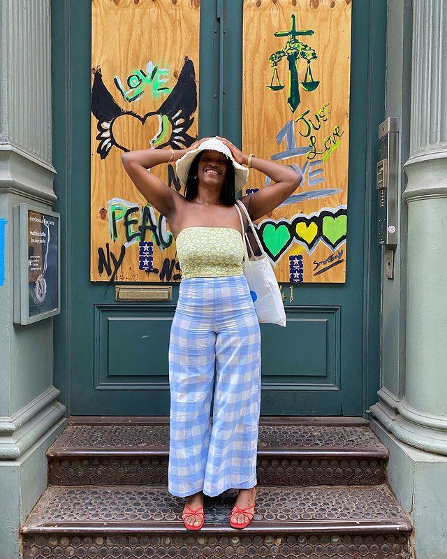 Garota usando top cropped sem alças verde com estampa floral e calça pantalona com estampa xadrez azul vichy. Ela ainda usa uma sandália vermelha, um chapéu bege e uma ecobag branca pendurada em um dos ombros. As duas mãos estão na cabeça e ela está sorrindo.