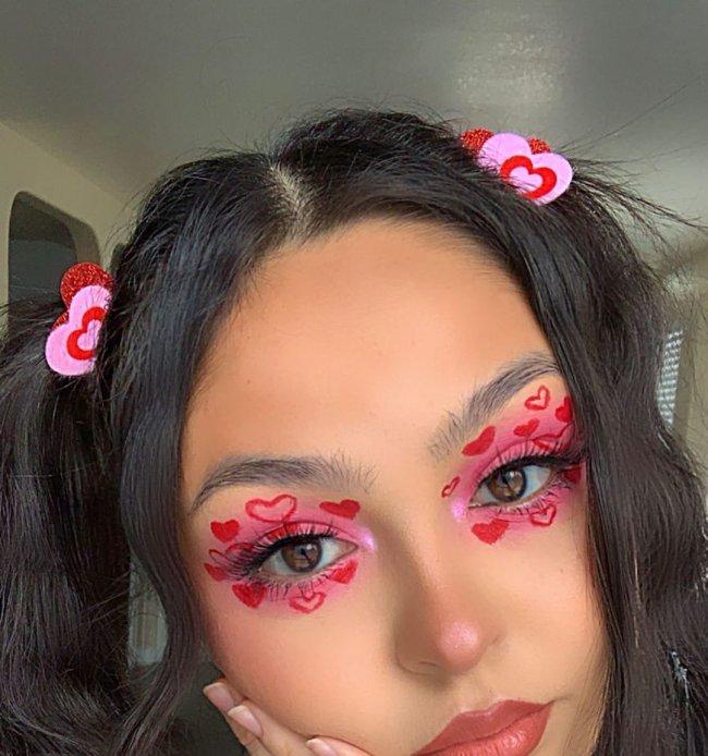 Jovem com uma das mãos apoiando seu rosto, com o cabelo preso em maria chiquinha de coração rosa e vemelho, com sombra rosa clara e vários corações vermelhos ao redor do olho, sua expressão é séria.