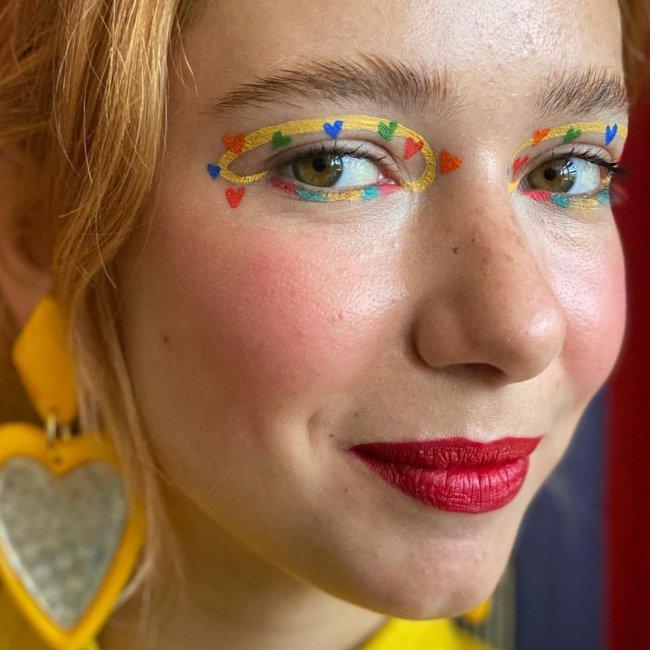 Jovem com o cabelo amarrado, brincos de coração amarelo, com maquiagem com sombra amarela e corações laranja e azul, nos lábios batom vermelho, olhando para a câmera com um quase sorriso.
