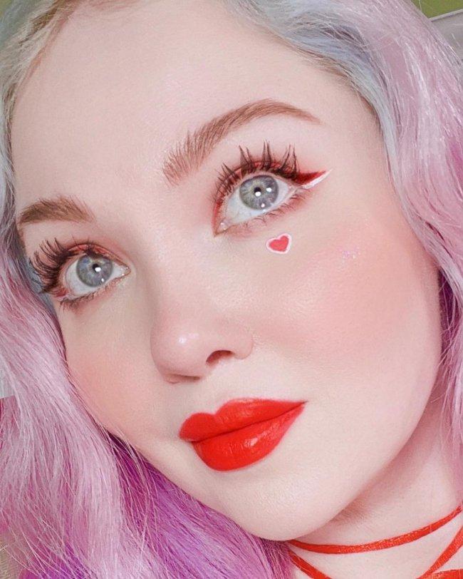 A imagem tem close no rosto da jovem onde só conseguimos ver uma parte de seu cabelo levemente cor de rosa, em seu rosto ela usa delineador vermelho, batom vermelho e tem um pequeno coração desenhado no lado direito de seu rosto abaixo dos olhos. Ela tem uma expressão sonhadora.