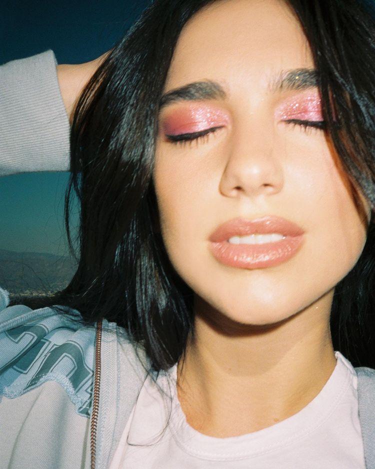 Dua Lipa usando maquiagem com sombra rosa de brilhos e gloss marrom. Ela está com os olhos fechados, boca levemente aberta e uma das mãos na cabeça.