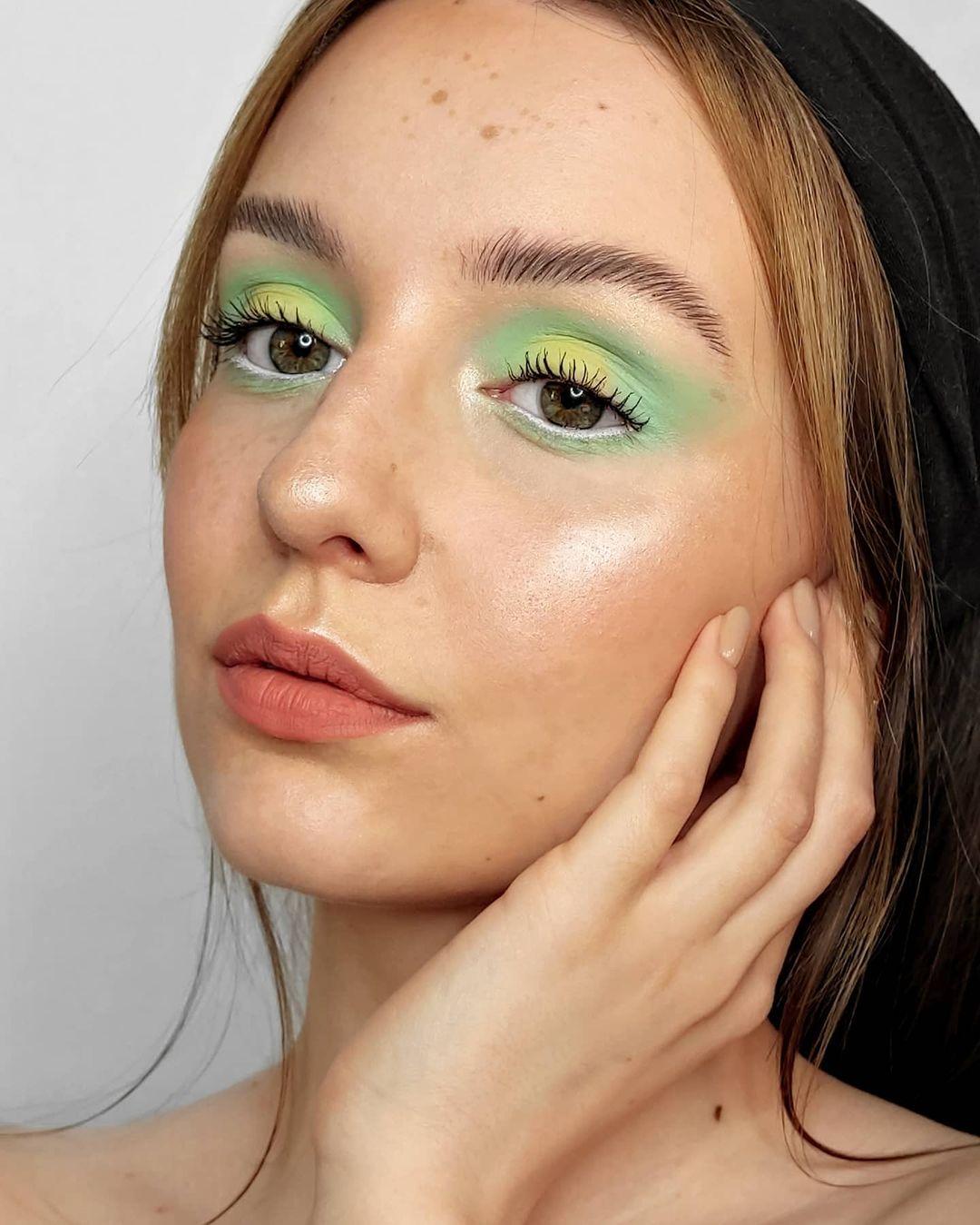 Garota usando maquiagem com diferentes tons de verde. Na foto, só dá para ver seu rosto e sua mão, apoiada no rosto. Ela está com a cabeça levemente voltada para o lado, expressão facial séria e olhando para o lado.