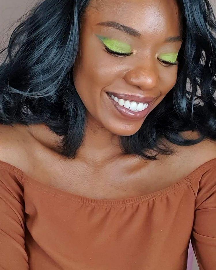 Garota usando sombra verde nos olhos e blusa marrom ombro a ombro. Ela está olhando para baixo e sorrindo. Seu cabelo é preto ondulado.