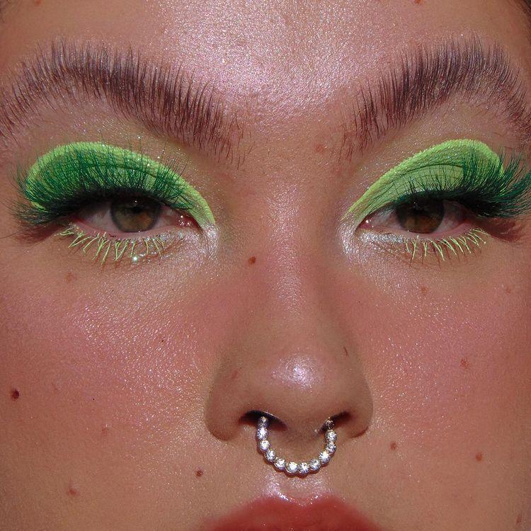 Garota usando maquiagem com dois tons de sombra verde: um mais escuro e outro mais claro. Na foto, dá apenas para ver o seu rosto. Suas sobrancelhas estão penteadas para cima, sua pele tem sardas, ela usa um piercing no septo e olha para a lateral.
