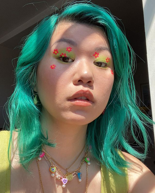 Garota usando maquiagem com sombra verde e florzinhas laranjas. Seu cabelo e sua regata são verdes e ela usa mix de colares. Ela está olhando para baixo, com expressão facial séria e boca levemente aberta.