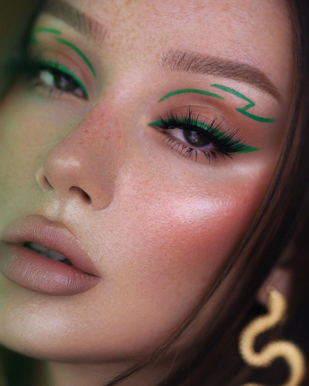 Garota usando maquiagem com delineado gatinho verde e um delineado gráfico na parte acima da pálpebra. Na foto, só dá para ver o rosto, que tem uma pele iluminada, blush bem mercado e batom cor de boca. A expressão facial é séria, com a boca levemente aberta.