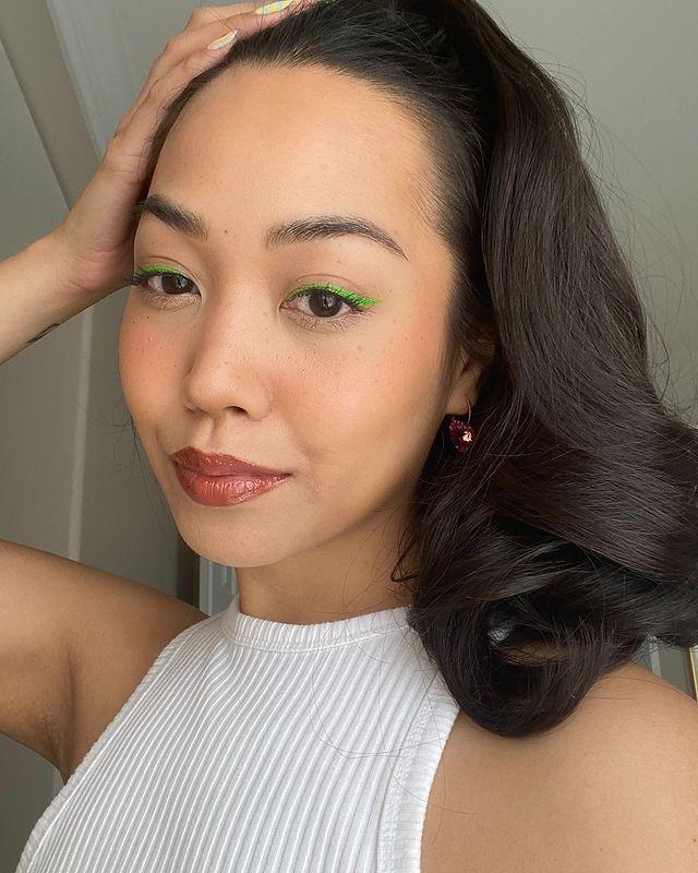 Garota usando blusa branca e delineado verde nos olhos. Uma das mãos está apoiada na cabeça e sua expressão facial é séria. Seu cabelo está preso em um rabo e na foto só dá para ver do ombro para cima.