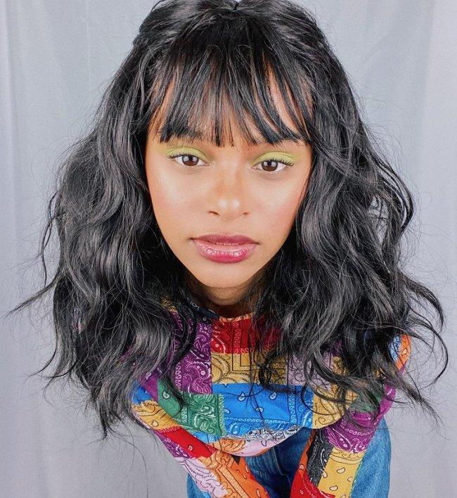 Garota usando blusa de manga comprida colorida e maquiagem com sombra verde. Ela está inclinada para a frente da câmera, sua expressão facial é séria e usa uma lace preta ondulada com franjinha.