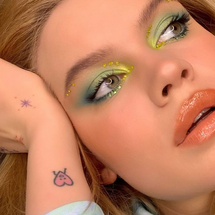Garota usando maquiagem com diferentes tons de verde. Na foto, só dá para ver seu rosto e uma mão apoiada na cabeça. Ela olha para o lado e a boca está um pouco aberta.