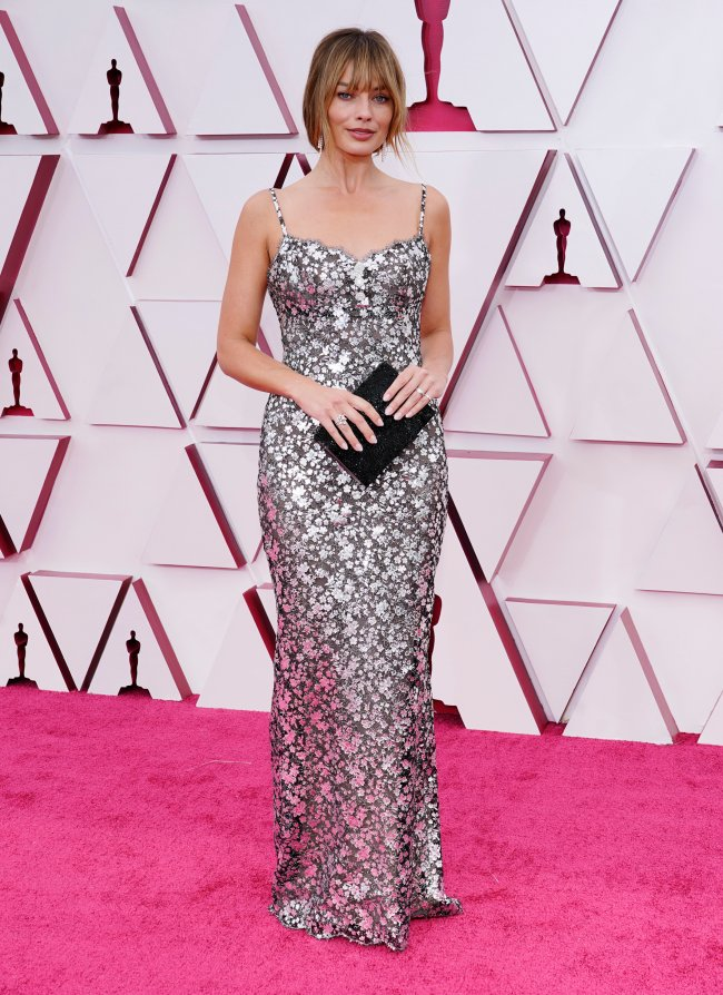 Margot Robbie no Oscar 2021. Ela está em pé, usando um vestido de renda de alcinha com estampa floral prateada e uma leve transparência. Ela está segurando uma clutch preta na frente do corpo com as duas mãos. Ela olha em direção à câmera com expressão facial séria.