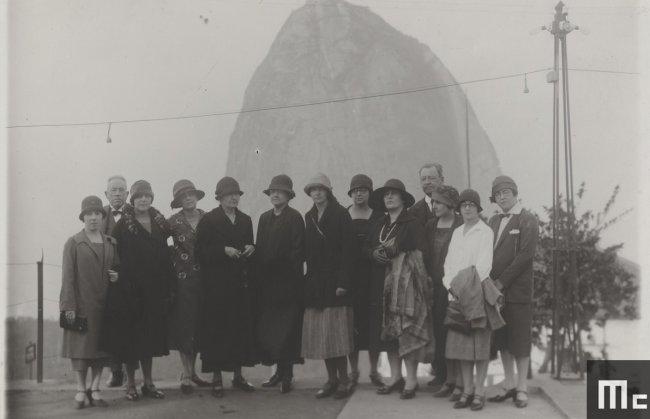 Foto em preto e branco da cientista Marie Curie durante visita ao Brasil; ela está rodeada de pessoas e o Pão de Açúcar aparece ao fundo