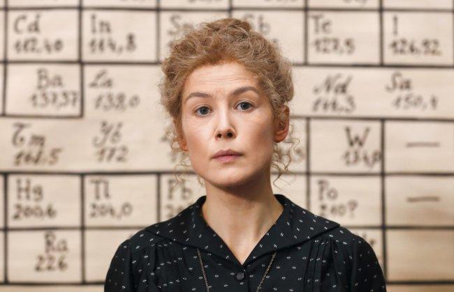 Foto de divulgação do filme Radioactive, protagonizado por Rosamund Pike; a atriz está caracterizada em frente a uma lousa preenchida com elementos químicos