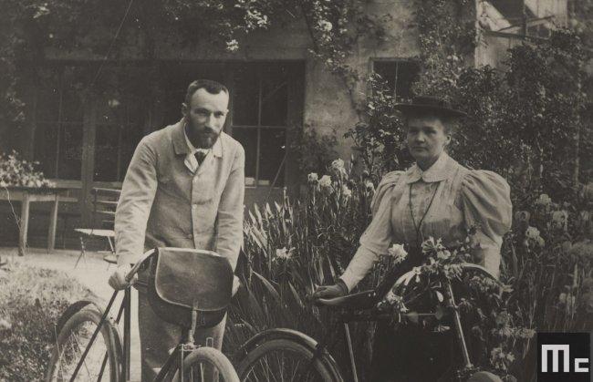 Foto em preto e branco da cientista Marie Curie andando de bicicleta com seu marido, Pierre, em Paris; eles posam para a foto em uma vilinha florida