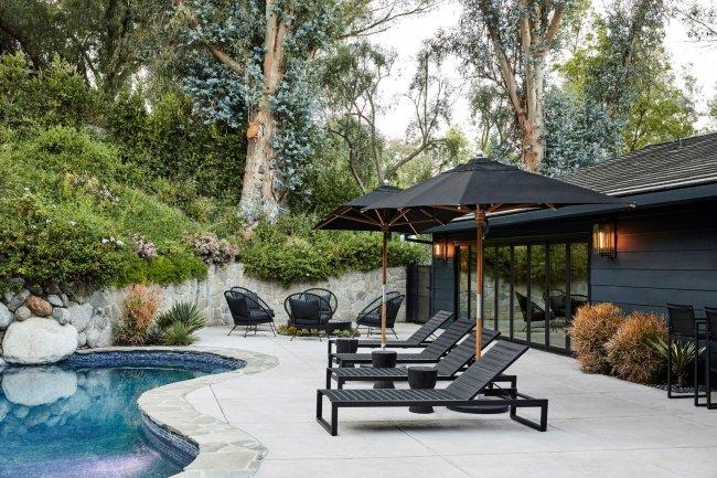 Área externa da casa de Miley Cyrus. Na imagem aparece três cadeiras pretas com guarda-sóis em primeiro plano, a piscina e ao fundo mais cadeiras pretas
