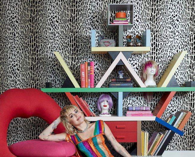 Miley ao lado de estante colorida com objetos que marcaram sua carreira, como duas perucas e um par de saltos. A cantora usa um vestido com listras coloridas e está apoiada em uma poltrona em formato de boca. Ao fundo, está um papel de parede de oncinha.