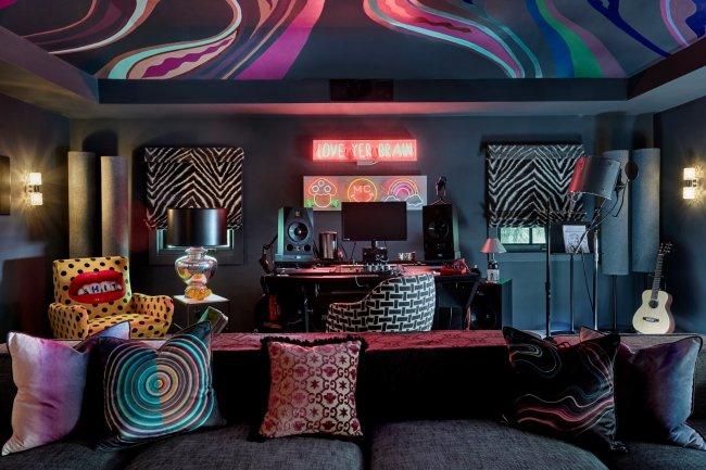 Estúdio na casa de Miley Cyrus. A imagem mostra um sofá com almofadas, letreiros luminosos na parede, quadros com estampa animal print e uma pintura no teto