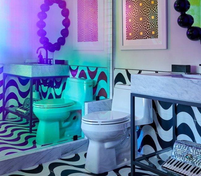 Banheiro da casa de Miley Cyrus. O ambiente tem azulejos em preto e branco e filme opaco do box do chuveiro./