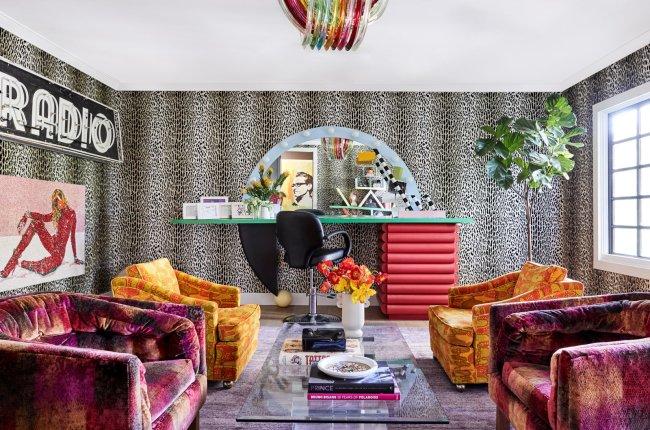 A imagem mostra uma das salas da casa de Miley Cyrus. A decoração é marcada pelo papel de parede de oncinha, sofás em vermelho e laranja, e um letreiro escrito