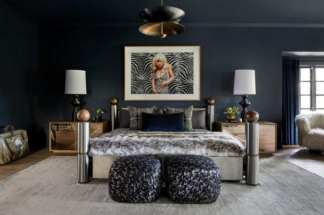 Quarto de Miley Cyrus. Na imagem, aparece uma cama de aço inoxidável, um quadro com a imagem de Debbie Harry e uma luminária em cada canto da cama. As cores que predominam a imagem são cinza, preto e azul marinho.