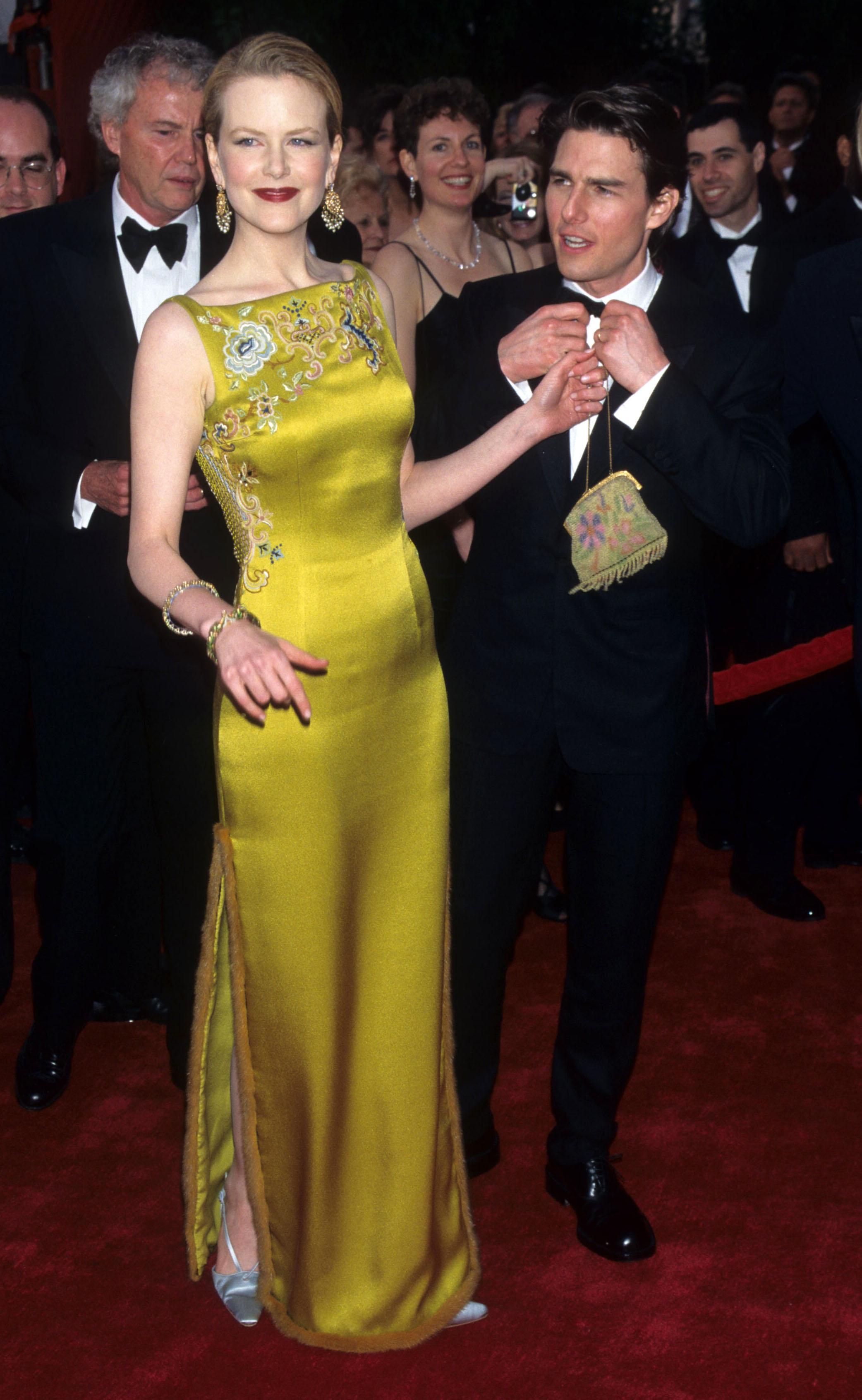 Nicole Kidman e Tom Cruise no tapete vermelho do Oscar de 1997. A atriz está usando um vestido longo dourado sem mangas, com fenda lateral e bordados na região do colo. Ela está sorrindo, sem mostrar os dentes, e segurando uma bolsa pequena dourada com uma das mãos. Tom Cruise está ao lado direito dela, com um terno preto e uma camisa branca, com as mãos mexendo na gravata borboleta, olhando para o lado enquanto fala.