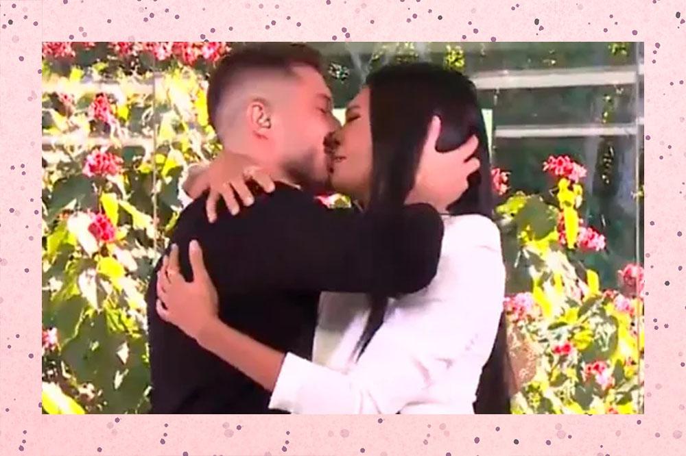 Ronan e Pocah se beijando no Mais Você; o produtor usa uma camiseta preta e a cantora um blazer branco
