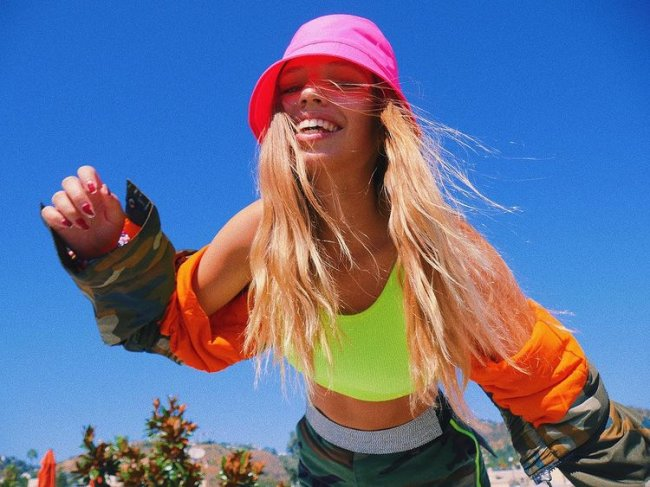 Cantora Salem Ilese, do hit Mad at Disney, posando para foto com cropped verde florescente, blusa de frio laranja com estampa do exército e bucket hat rosa