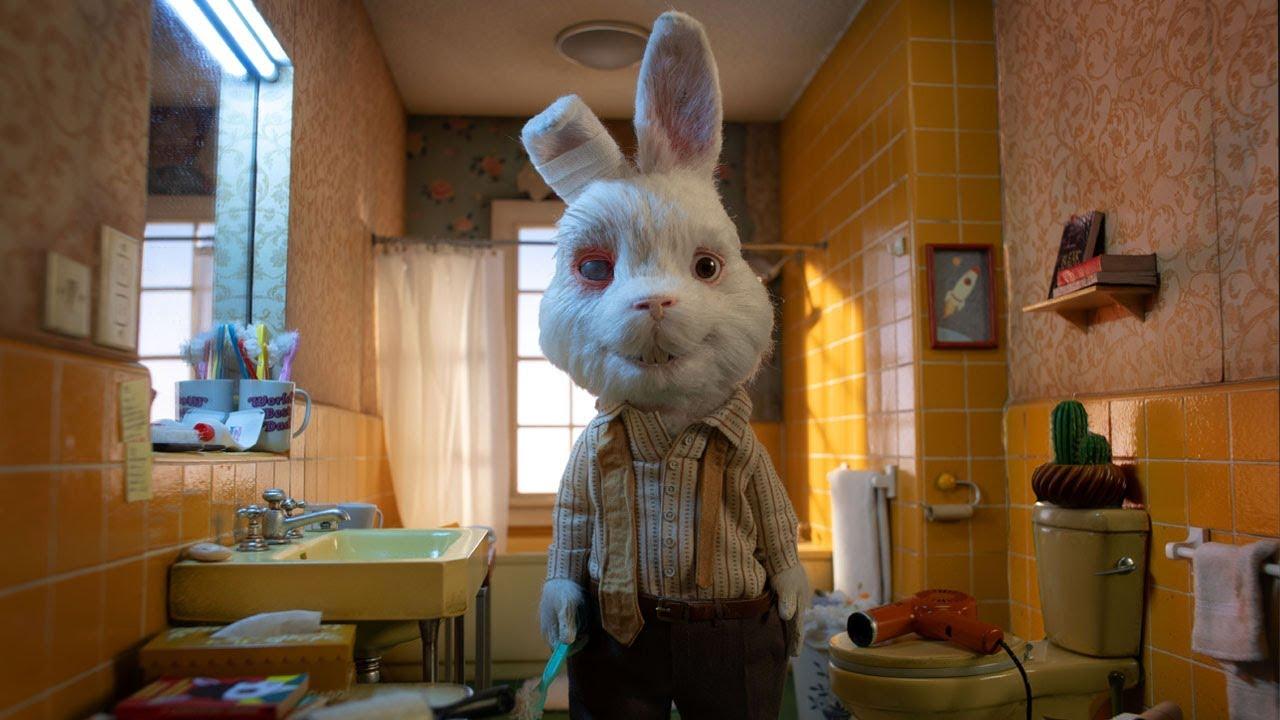 Cena do curta-metragem de animação Salve O Ralph. O Ralph, um coelho, está no banheiro de sua casa. Ele está olhando para a câmera, um de seus olhos está vermelho, e uma de suas orelhas com curativos. Ele usa uma camisa bege de botões na frente, uma calça marrom e uma gravata desamarrada ao redor do pescoço. Com uma das mãos, ele segura uma escova de dentes.