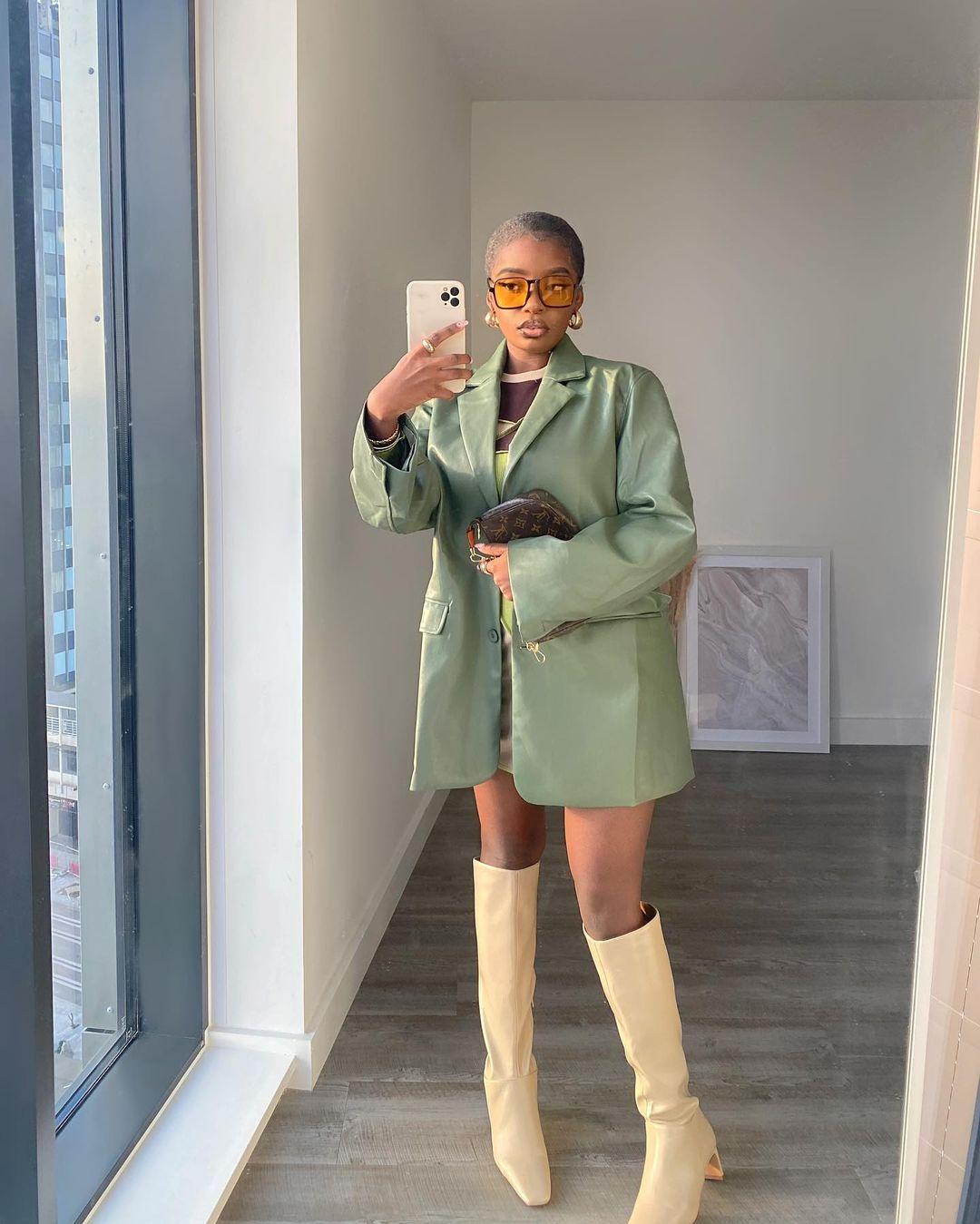 Mulher usando casaco verde de couro com bota bege de bico quadrado que vai até o joelho e óculos de sol de lentes alaranjadas. Ela está em pé em frete a um espelho, segurando o celular com uma das mãos.